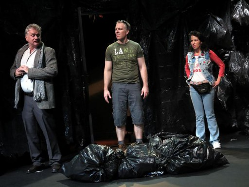 "IATI Theater, 64 East 4th Street, NYC presents the world premiere of ""Storage Locker"" by Jeff Stolzer, directed by Julián J. Mesri, October 7 to 30, 2016. In this dark comedy, a married couple gets a lot more than they bargained for when bidding on somebody's dusty old stuff in an auction at a self-storage facility. (R) Bryn Packard and Nicole Betancourt as the couple, (L) David Crommett as the older man who tries to buy back the contents of the unit. Photo by Jonathan Slaff."